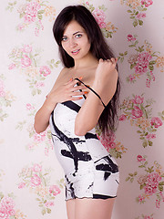 Gorgeous dark haired teen taking off clothes and posing in the nude with a painting frame.