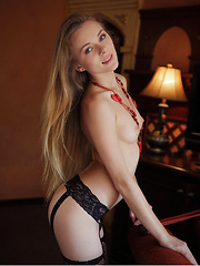 Wearing a sexy black garter belt with   matching thigh-high fishnet stockings,   Katie makes a tempting presence in the   living room, posing without any hint of   inhibition.