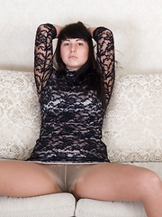 Tayra Jane strips naked by her grey sofa